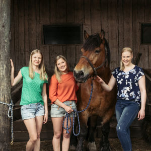Kolme eläinlääketieteen kandia poseeraa kameralle hevosen kanssa