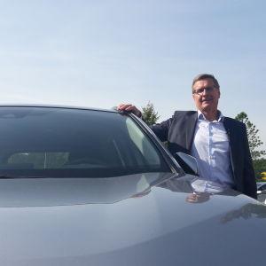 Vd Pekka Rissa vid Bilhandelns centralförbund poserar vid en bil.