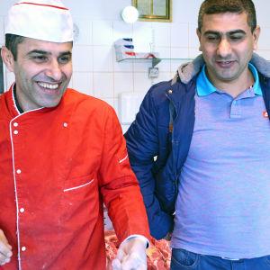 Två män står framför köttdisk