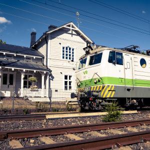 VR:n valko-vihreä juna ajaa raiteilla, taustalla valkoinen asemarakennus.