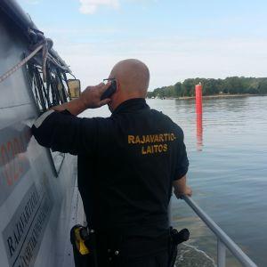 En sjöbevakare står på en patrullbåt och får ett samtal om en olycka till sjöss.