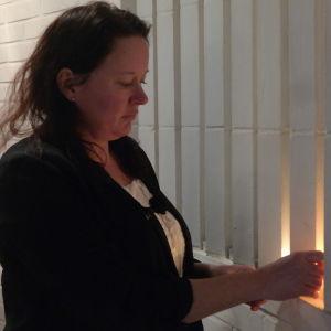 Johanna Sjöberg tänder ljus i ett begravningskapell