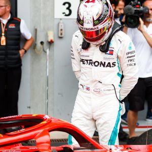 Lewis Hamilton inspekterar en Ferrari-bil.