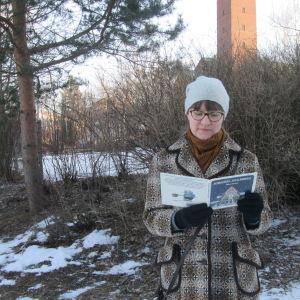 Kirjabloggaaja Liisa Pihlaja lukee talvisessa säässä Mauri Kunnaksen Koiramäen joulukirkkoa.