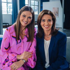 janina Fry och Ira Hammermann sitter i en grå soffa och ler brett mot kameran.