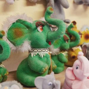 Erivärisiä norsukoristeita tai -leluja hyllyllä. Norsuilla kärsät pystyssä.