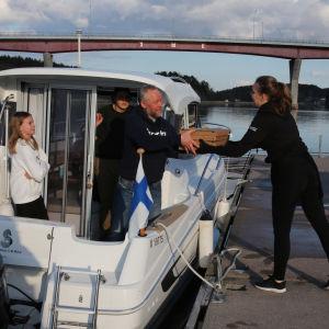 En servitör ger hämtpizzor från bryggan till en båt i Merimasku.
