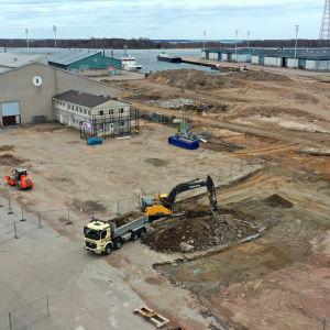 Kaivuri nostaa maa-ainesta kuorma-auton kyytiin Kotkan Kantasataman työmaalla