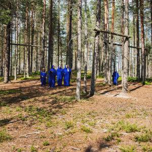 siniseen kaapuun pukeutuneita naisia Soivassa Metsässä Suomussalmella.