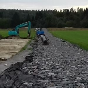 Ett gasrör grävs ner rakt över en åker.