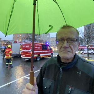 Medelålders man står under grönt paraply. Bakom honom på gatan syns en brandbil.