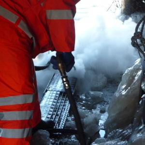 en person i orangea arbetskläder smälter is i ett trångt utrymme