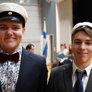 Två unga män med studentmössor. I bakgrunden skymtar Finlands flagga. De är i en gymnastiksal.