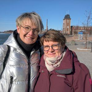 två kvinnor vid strandpromenad