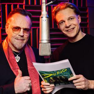 Pertti Neumann ja Olli Riipinen seisovat molemmin puolin katosta roikkuvaa mikkiä äänitysstudiossa hymyillen.