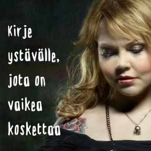 Studiossa otetussa kuvassa Katja Kettu pitelee käsissään teko-korppia.