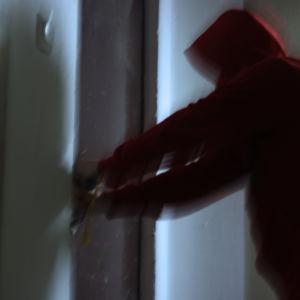 En person gör inbrott.