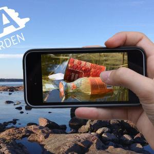 Hand fotograferar skräp i skärgården med en mobiltelefon