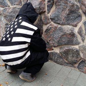 Ung kille med ryggen mot kameran vid stenvägg.