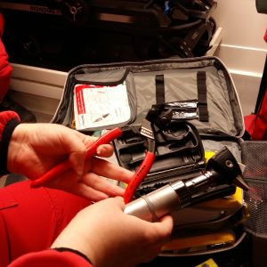 Akutvårdaren visar upp en avbitartång och en öronlampa som hör till utrustningen för ambulansen.
