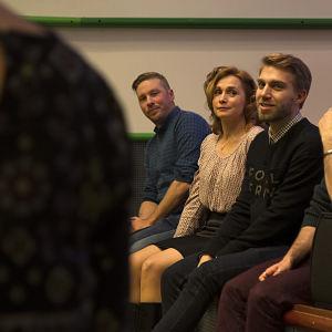 Syke-sarjan näyttelijät istuvat lavan reunalla.