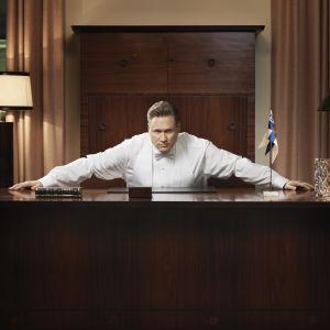 Pöydän äärellä vakavana istuu Samuli Edelmann, hän on roolissaan Henri Talviona sarjassa Presidentti.
