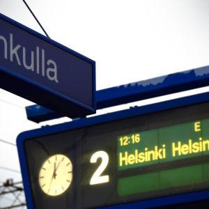 Järnvägsskylt: Grankulla, samt tågtidtabellsskylt som annonserar tåg mot Helsingfors.