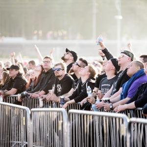 Publik från Rock Fest som pekar mot himlen