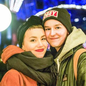 Olivia och Emil står tätt ihop och tittar in i kameran. I bakgrunden syns en massa lysande lampor.