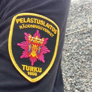 Närbild av ärmen på en brandman, räddningsverkets logga är insydd i skjortan.