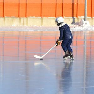 ett barn spelar ishockey