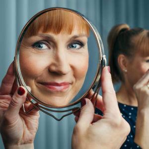 Nainen katsoo peilin kautta kameraan