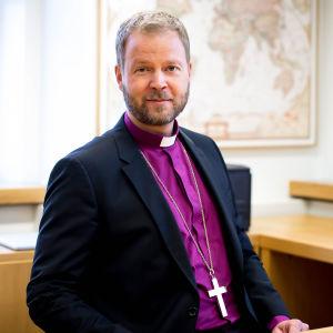 Piispa Teemu Laajasalo istuu työpöytänsä ääressä
