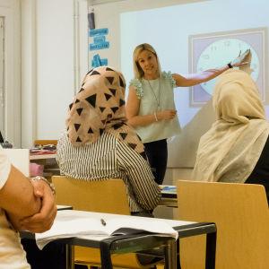 Opettaja näyttää taululta kellonaikoja ja oppilaat katsovat