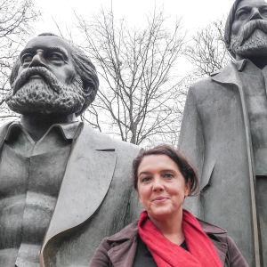 Historioitsija Bettany Hughes Marxin ja Engelsin patsaalla Berliinissä