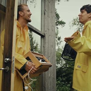 Kasper och Jussi Virta i gula regnrockar vid dörren till en stuga