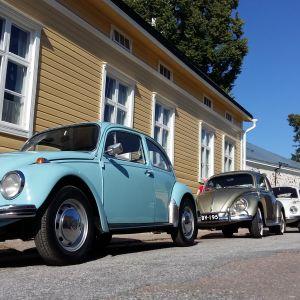 Tre Volkswagen bubblor i rad utanför Ekenäs kyrka, en ljusblå, en guldfärgad och en vit.