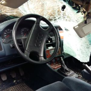 Bild inifrån en bil som kört på en älg. Hela högra sidan av vindrutan är intryckt och krossad.