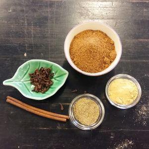 Några små burkar med kryddor på en svart bänk.