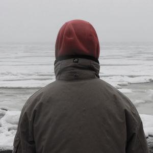 En bild på en man som tittar ut över vattnet.