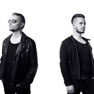 Kaksi miestä seisoo mustavalkoisessa kuvassa valkoisen seinän edessä, toisella aurinkolasit päässä, toinen katsoo sivusilmällä kameraan. Pukeutuneet tummiin vaatteisiin.
