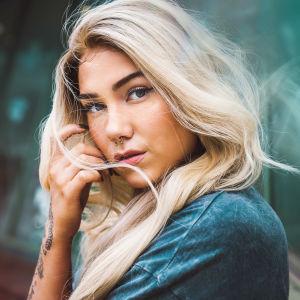 Vaaleahiuksinen laulaja Eveluna katsoo tuulessa heiluvien hiustensa takaa kameraan. Hän seisoo kameraa kohti sivuttain ja nojaa toista kättään kevyesti poskeensa.