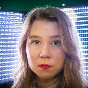 Emilia Laurila katsoo kameraan ja taustalla sinisiä valoja