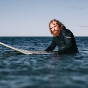 Kristofer Hivju som Erik står till midjan i vattnet med surbräda. Inga vågor.