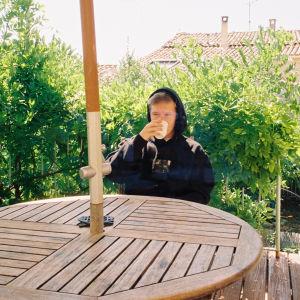 Nuori mies istuu pihapöydän ääressä ja juo kupista, taustalla näkyy puskia ja taloja. Miehellä on musta huppari päällä ja huppu päässä.