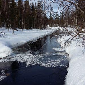 En bred bäck med lite is på i ett snöigt vinterlandskap.