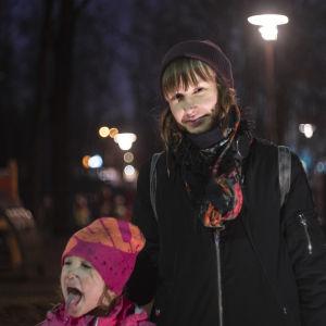En kvinna står ute på kvällen utanför en lekpark. Hon ser in i kameran allvarsamt.