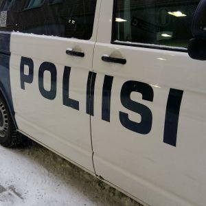 En polisbuss på en snöig gata.