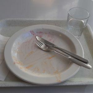 En bricka med glas, servett, bestick och en tallrik där all mat är uppäten.
