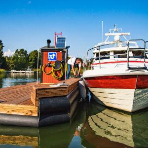 Mies kiinnittää venettä imutyhjennuslaitteeseen.